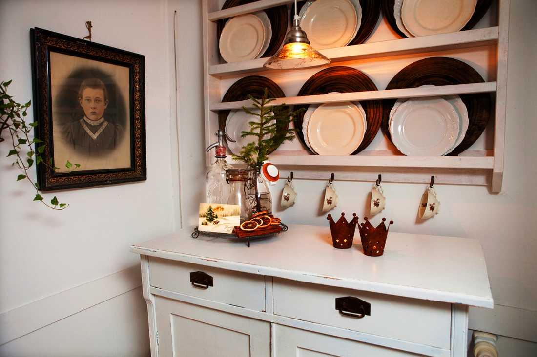 FÖRSTUGA/HALL. Tallrikshyllan har Maris pappa tillverkat, trätallrikarna är en present av Johnny. Ljuslyktorna i form av kronor är från Falu antik & Diversehandel. Kopparna som hänger på krokar är från Hackefors.