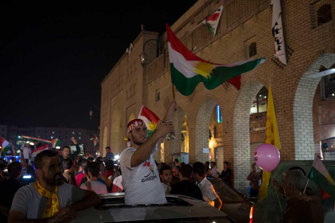 En man viftar med en kurdisk flagga utanför en vallokal.