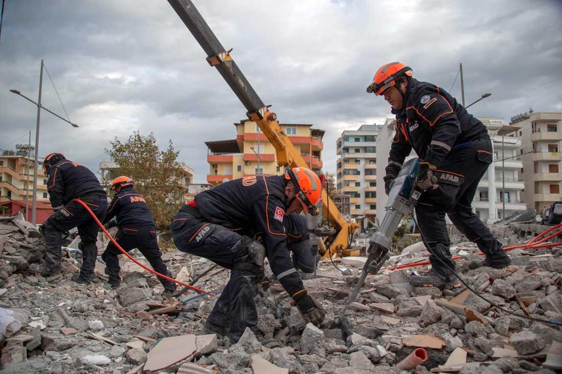 Turkiska räddningsarbetare genomsöker en raserad byggnad i hamnstaden Durrës i Albanien på torsdagen.