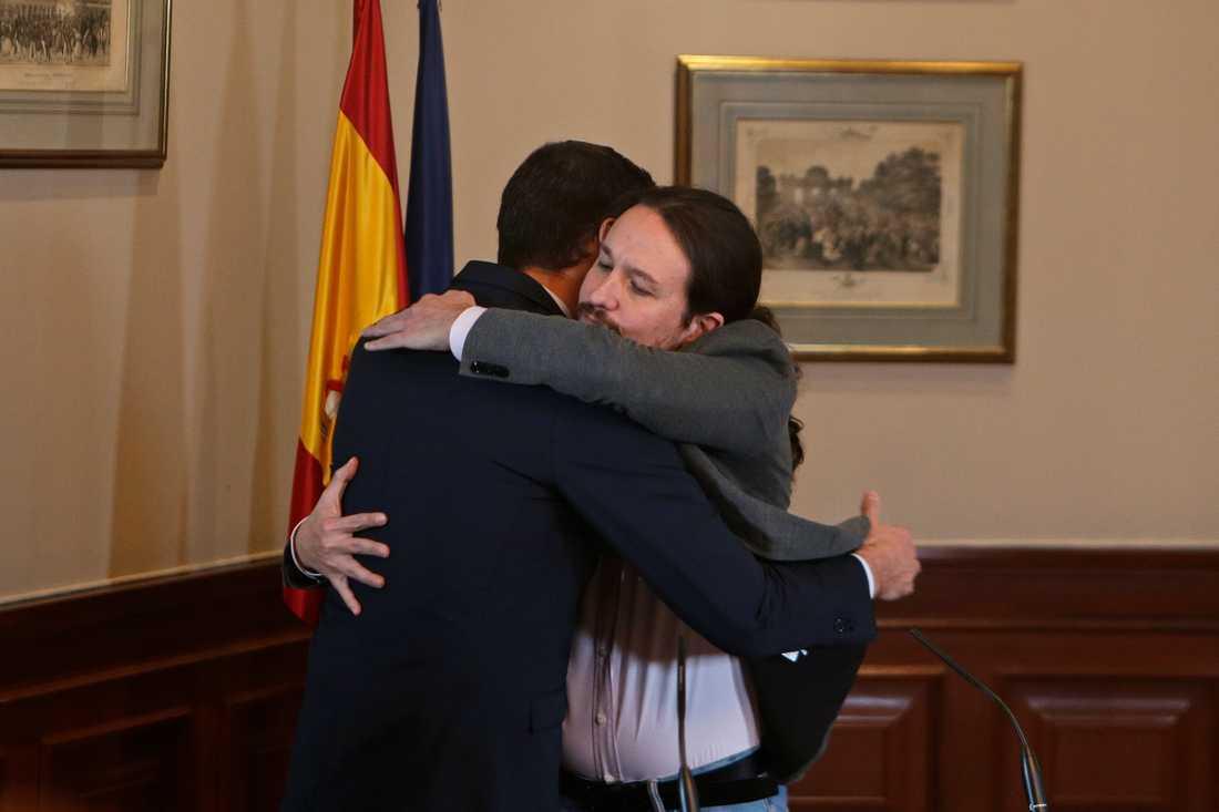 Spaniens tillförordnade premiärminister Pedro Sánchez (tv) kramas med Unidas Podemos-ledaren Pablo Iglesias efter att ha skrivit under en pakt om att bilda en koalitionsregering.