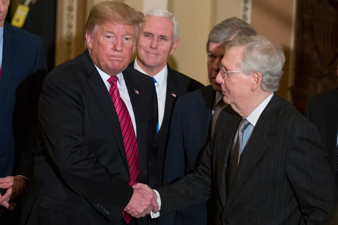 USA:s president Donald Trump skakar hand med senatens majoritetsledare, partikamraten Mitch McConnell. I bakgrunden syns vicepresident Mike Pence.