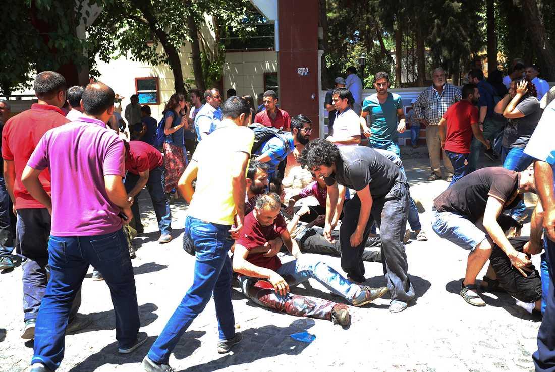 Människor hjälper skadade på gatorna.