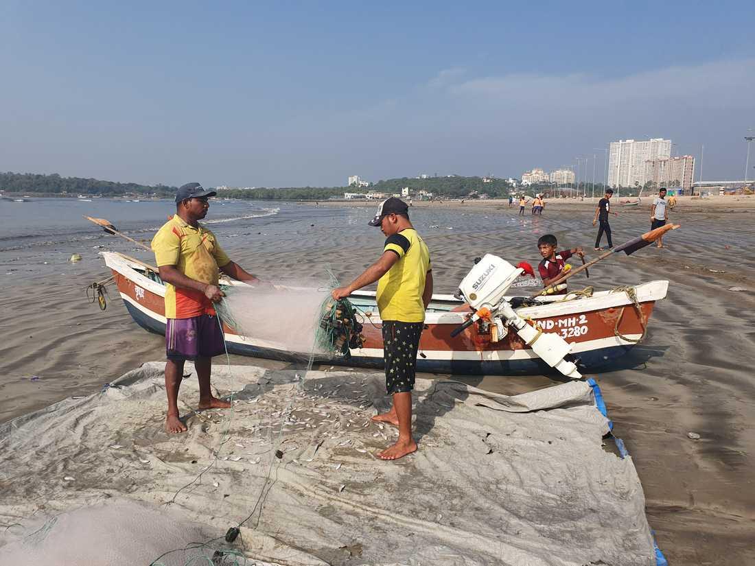 Versova beach i Mumbai. Fiskare tömmer sina nät några hundra meter bortom den iscensatta städdagen.