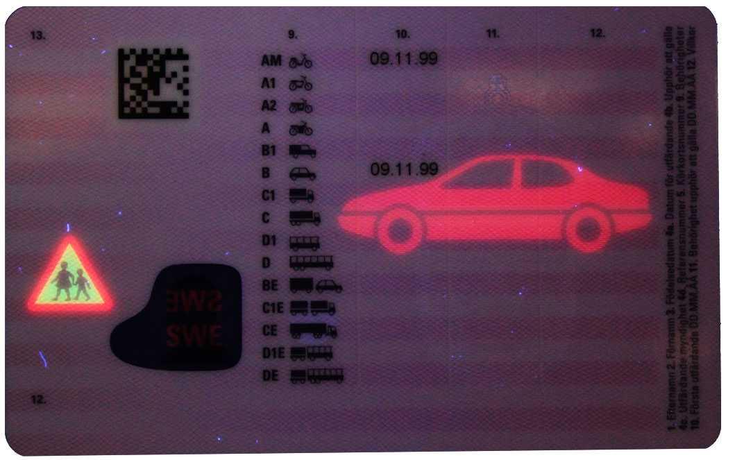"""På baksidan av kortet syns en röd bil samt en """"Varning för barn-skylt"""" – för den som har UV-lampa."""