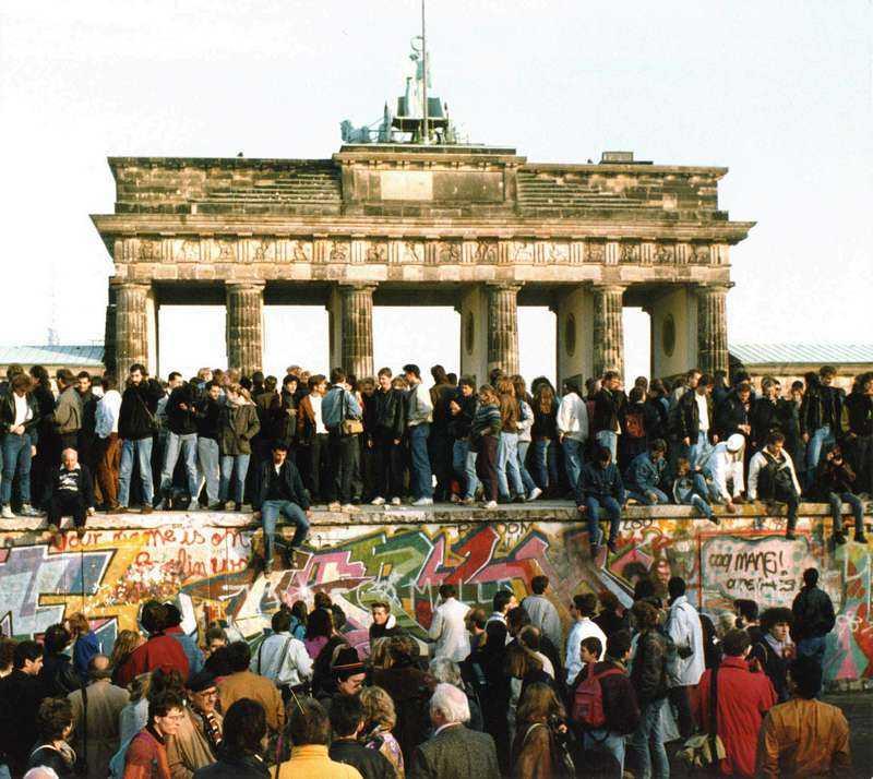 Tyskar på muren vid Brandenburger Tor en dag efter att muren öppnades.