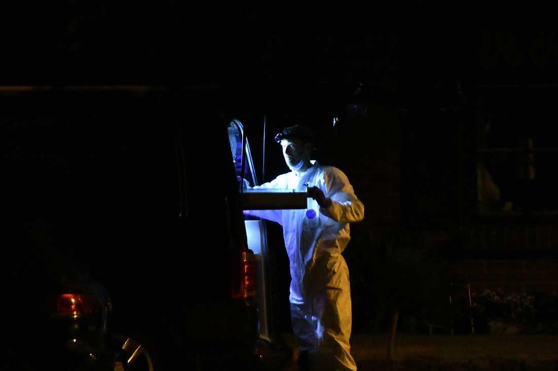 Teknikerna hade vita dräkter och bar ut saker i påsar, uppger ett vittne på plats.
