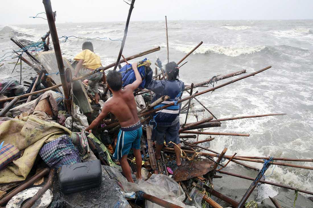 En familj försöker rädda tillhörigheter från sitt hus vid kusten.