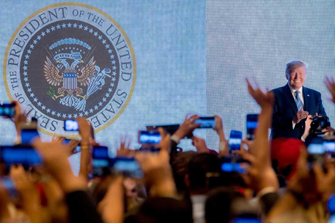 Donald Trump framför studenterna, med det felaktiga sigillet bakom sig.