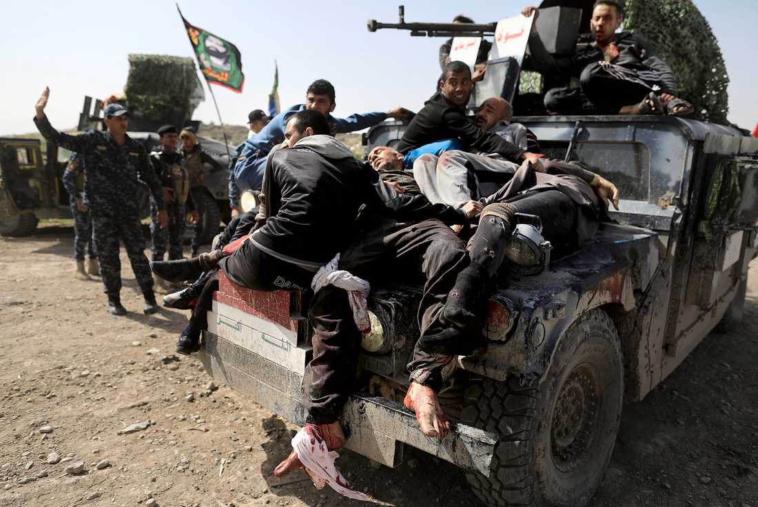 Irakisk federal polis tar hand om skadade civila i västra Mosul.