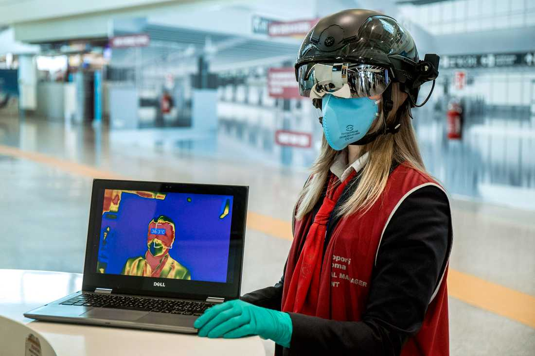En medarbetare vid Romflygplatsen Leonardo da Vinci använder sig av en så kallad smarthjälm för att mäta kroppstemperaturen hos passagerare.