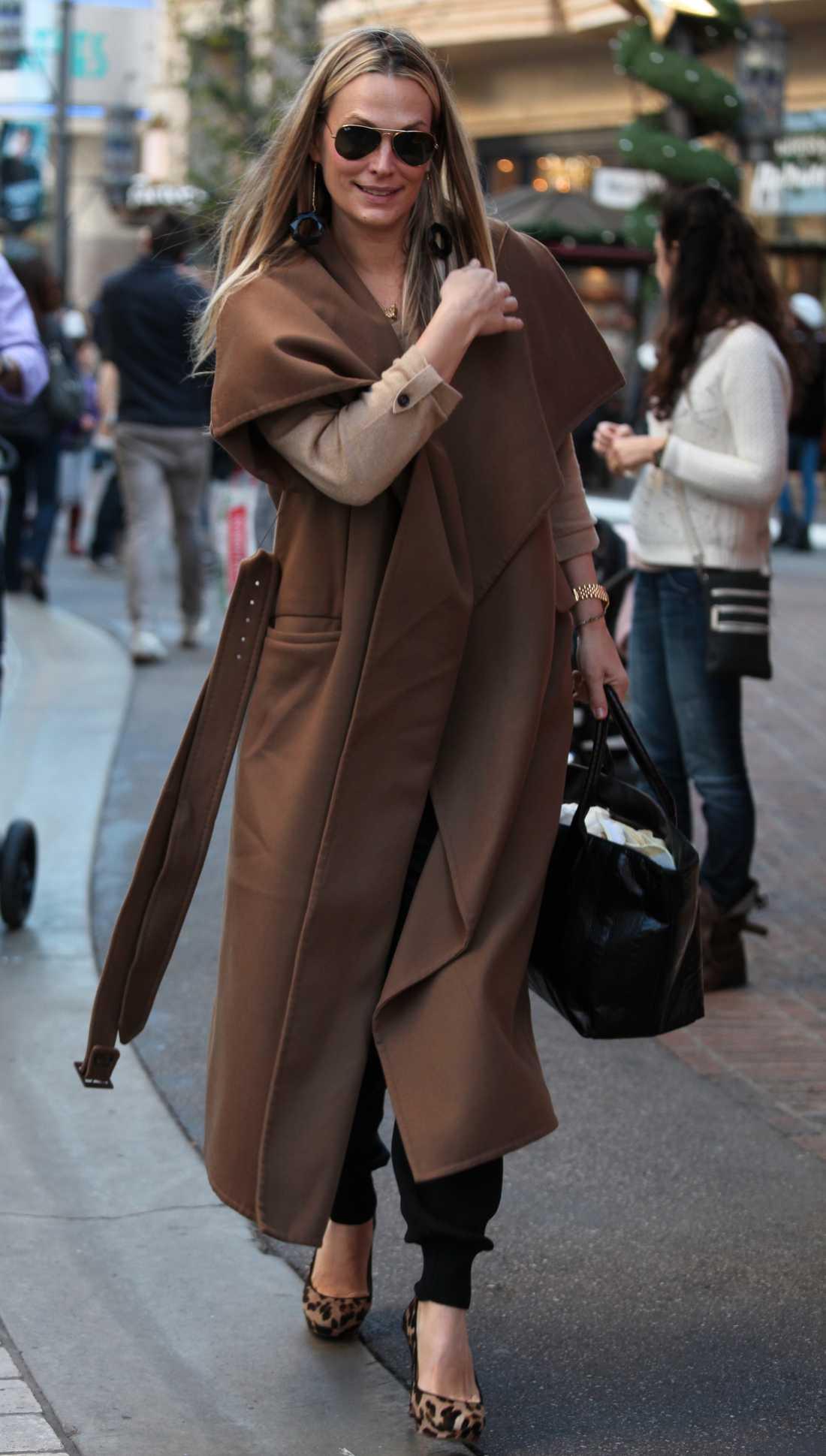 Molly Sims slänger och flänger i lång, brun kappa och leopardpumps.