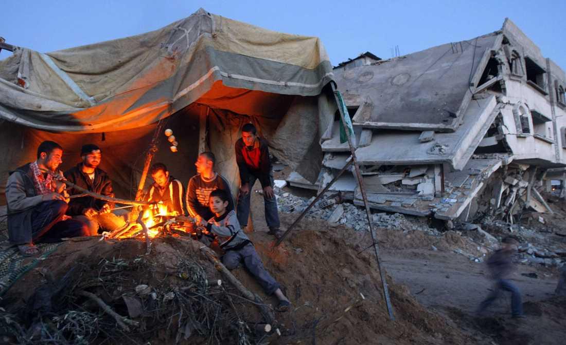 Många behövande På bilden ses palestinier sitta i ett provisoriskt uppsatt tält. Bostaden är förstörd. Nu kräver USA:s president Barack Obama att Israel öppnar gränsövergångarna till Gaza men frågan är infekterad.