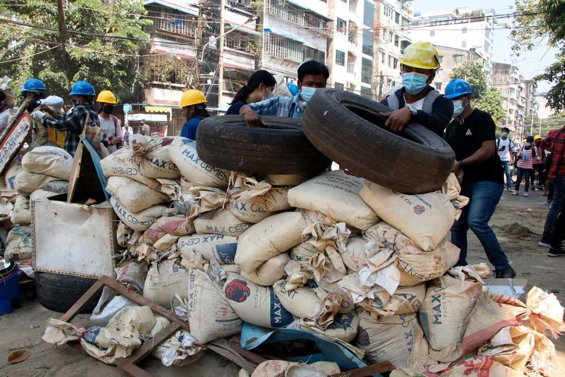 Demonstranter bygger barrikader i Rangoon.