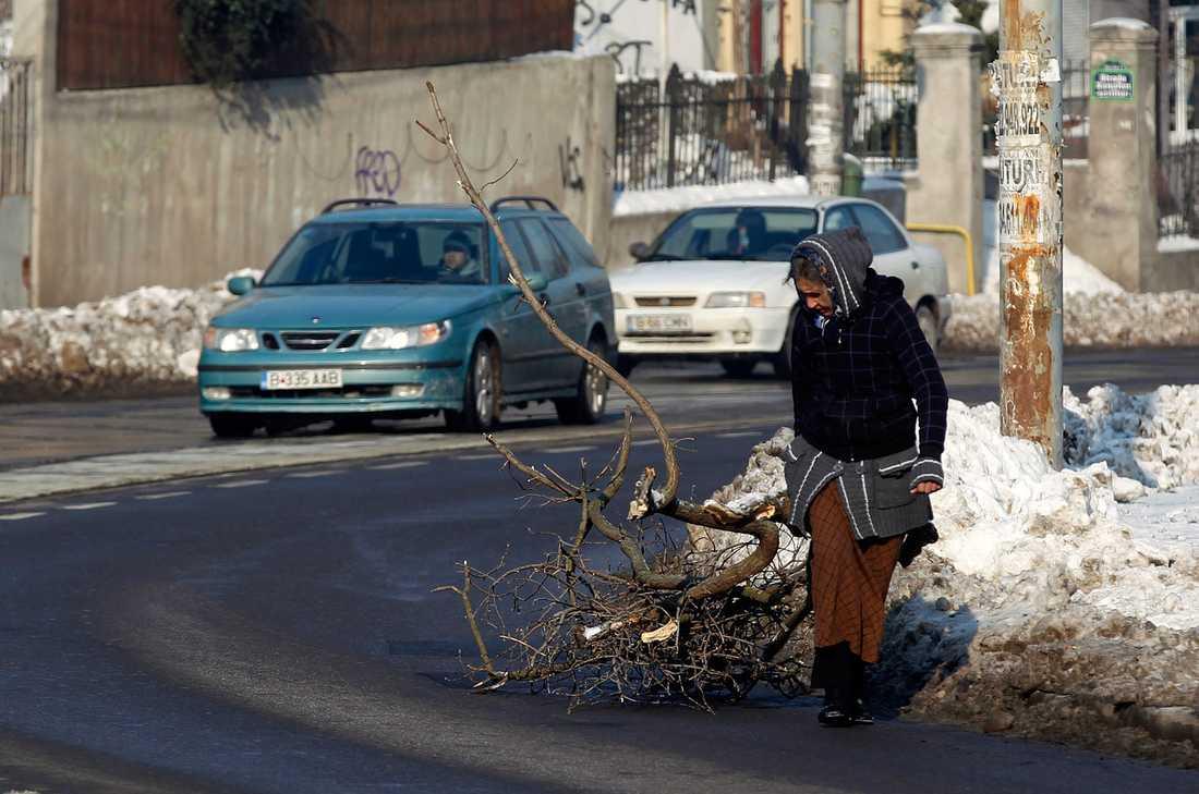 En kvinna letar bränsle i Bukarest.