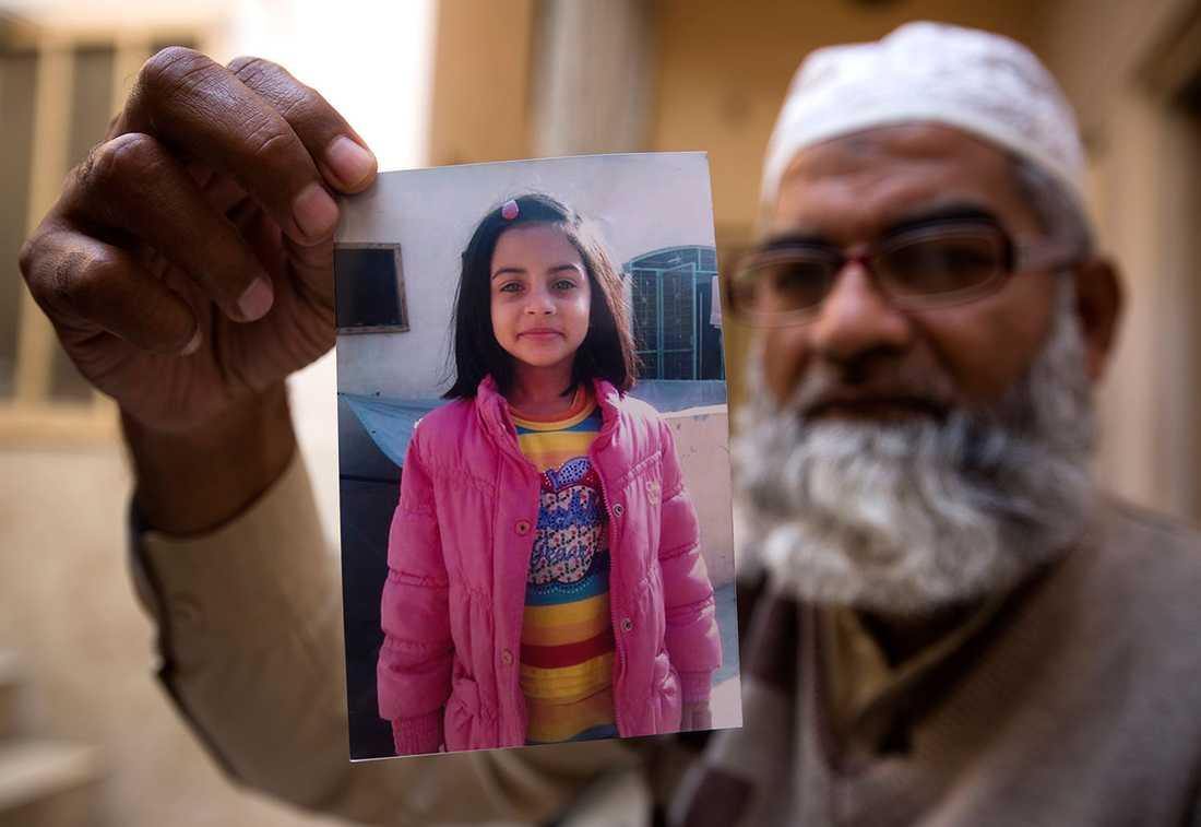 Mohammed Amin håller upp en bild på sin mördade dotter, Zainab Ansari, 7.