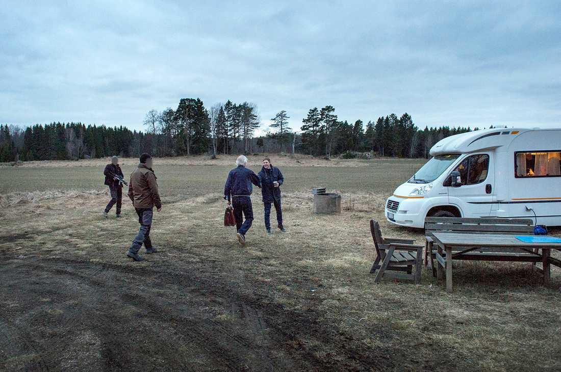 CIRKUS VILKS Lars Vilks (med väskan) anländer i bilkortege till det hemliga mötet som ska hållas i en husbil på Uppsalaslätten. På plats finns ett 30-tal poliser, två bombhundar och en helikopter.