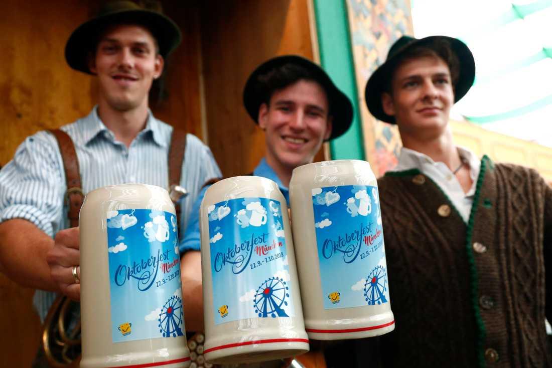 Musikerna Sepp, Andreas och Quirin visar upp årets officiella Oktoberfest-mugg.