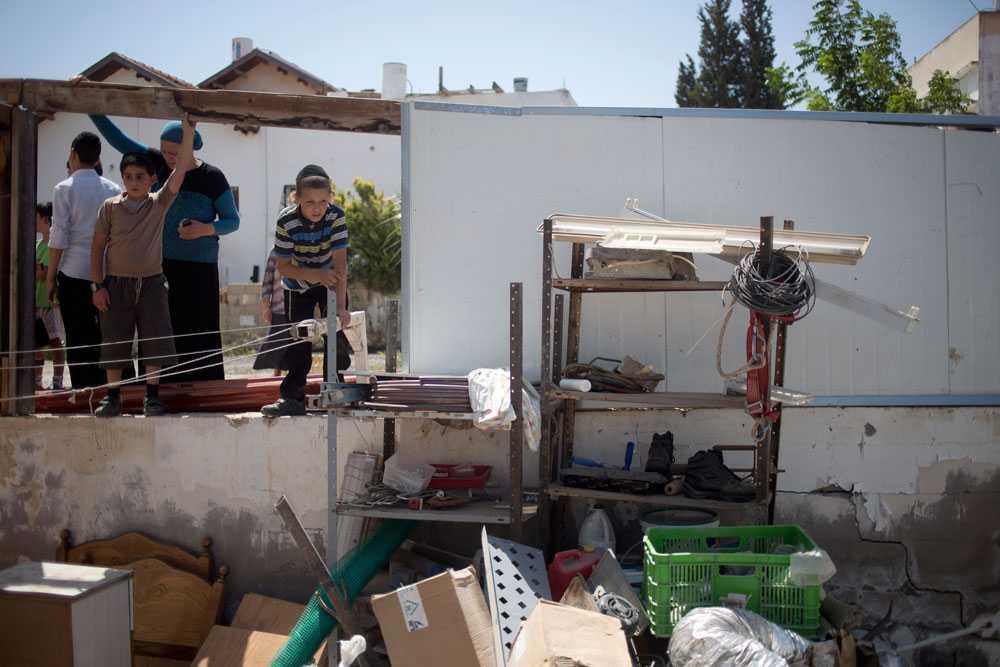 Hamas svarar med nya beskjutningar. Israeliska pojkar i Netivot tittar på skadorna efter en raket skjuten av Hamas.