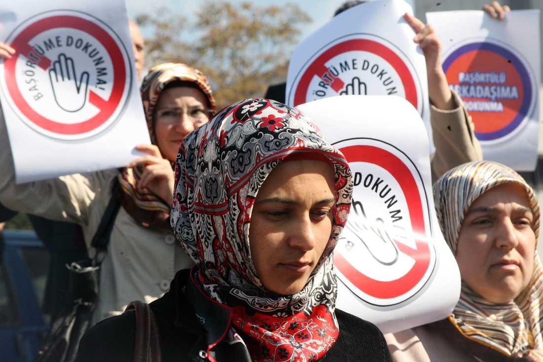 """Kvinnor protesterar inför turkiets högsta domstol 2008 strax innan förbudet mot slöja lyftes. """"Rör inte min huvudduk"""" står det på affischerna."""