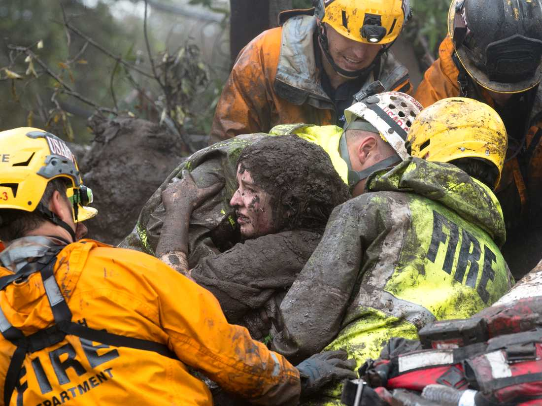 Räddningspersonal räddar en kvinna ur ett kollapsat hus.