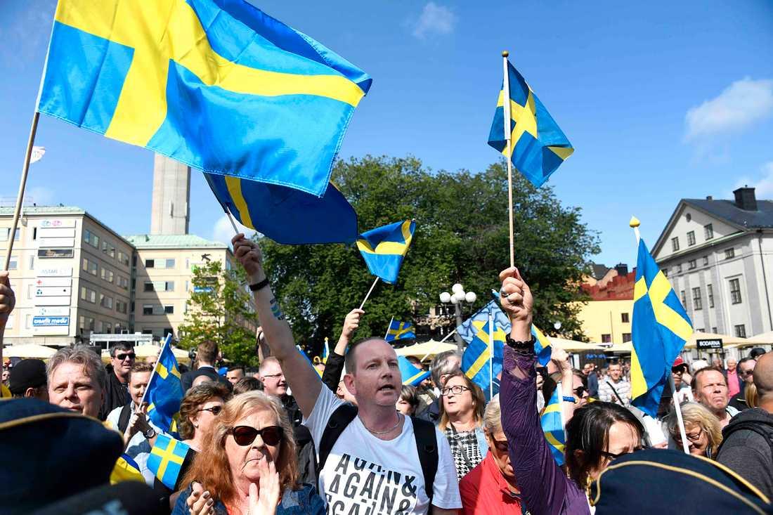 Sverigedemokrater skändar flaggan med skamlöshet på Medborgarplatsen, Stockholm, lördag 19 augusti.