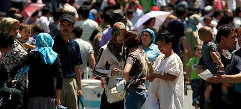 På väg Människor trängs med sina tillhörigheter på en busstationen i Ürümqi.