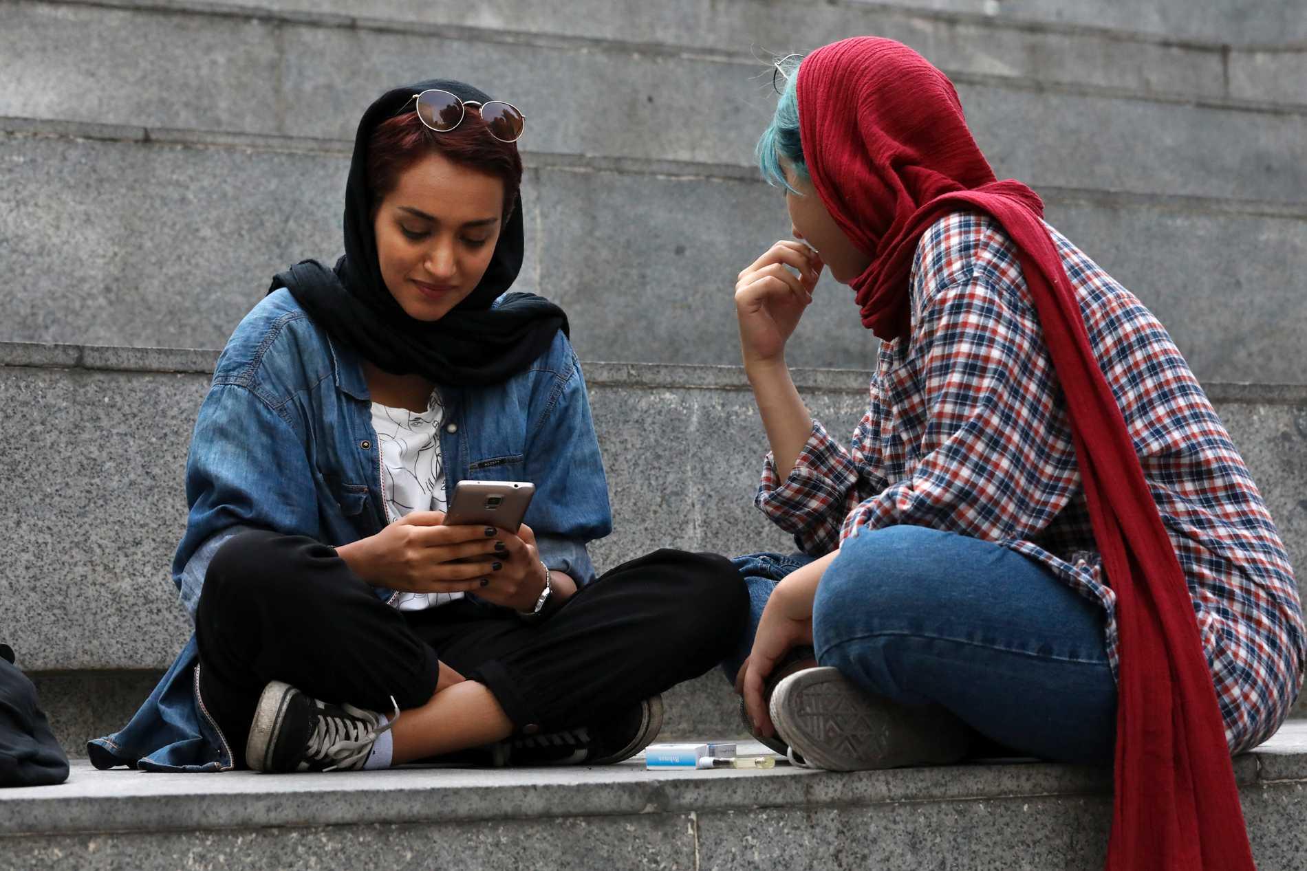 En ung kvinna kollar sin mobil i Teheran. Står kärleken att finna i flödet? Arkivbild.