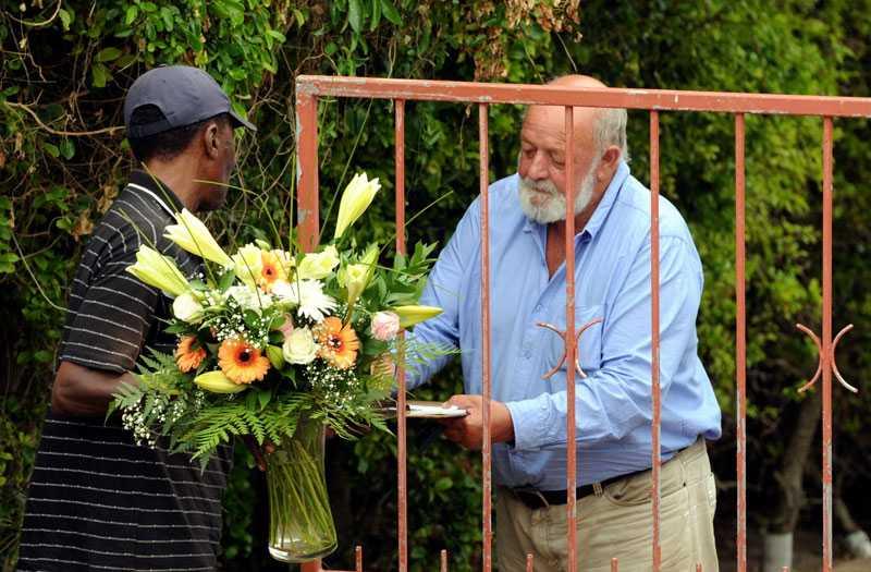 Samtidigt som häktesförhandlingen äger rum begravs Reeva Steenkamp på annat håll. Här får hennes pappa ta emot blommor utanför hemmet i Seaview.