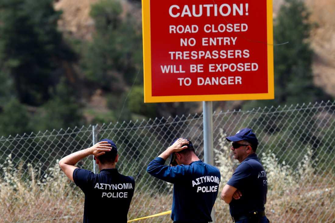 Poliser utanför en konstgjorda sjön utanför staden Nicosia. Den misstänkte mördaren uppges ha erkänt att han dödat fem kvinnor och två flickor och dumpat deras kroppar.