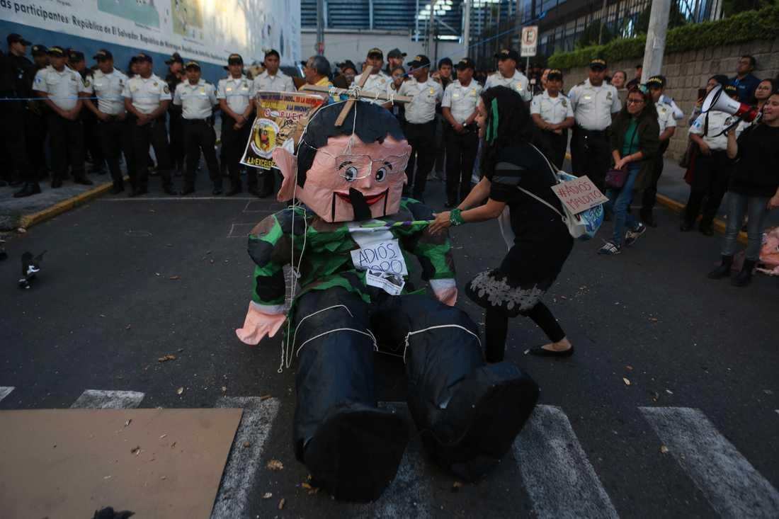 En demonstrant slår på en docka föreställande den avgående korruptionsanklagade presidenten Jimmy Morales under protester i huvudstaden Ciudad de Guatemala på tisdagen.