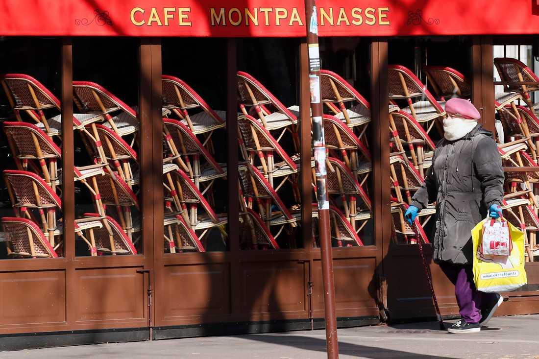En kvinna går förbi en tillfälligt stängd restaurang i Paris. Arkivfoto.