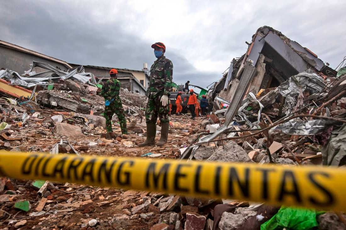 Räddningsarbetare letar efter offer i resterna av en kollapsad byggnad i Mamuju på västra Sulawesi i Indonesien.