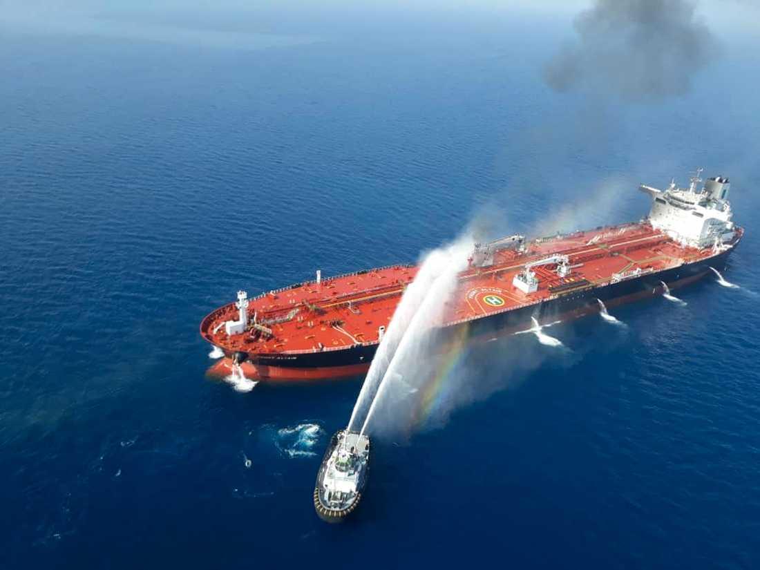 En båt från den iranska flottan i släckningsarbete vid ett av de attackerade fartygen. Bilden publicerades av den iranska nyhetsbyrån Tasnim.