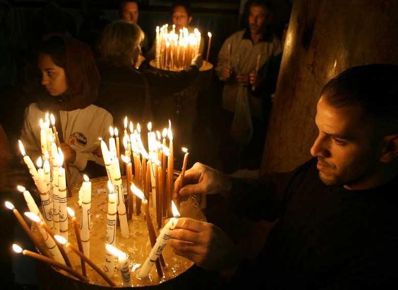 TRADITION Kristna pilgrimer tänder ljus i Födelsekyrkan i Betlehem på västbanken. Foto: AP