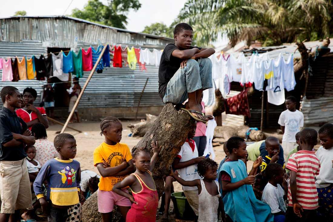 Barnen i centrala New Krutown flockas för att se när begravningsteamet arbetar, när de bär ut ännu en död kropp ur deras grannars hus. Skolorna i liberia har varit stängda sedan utbrottet började.