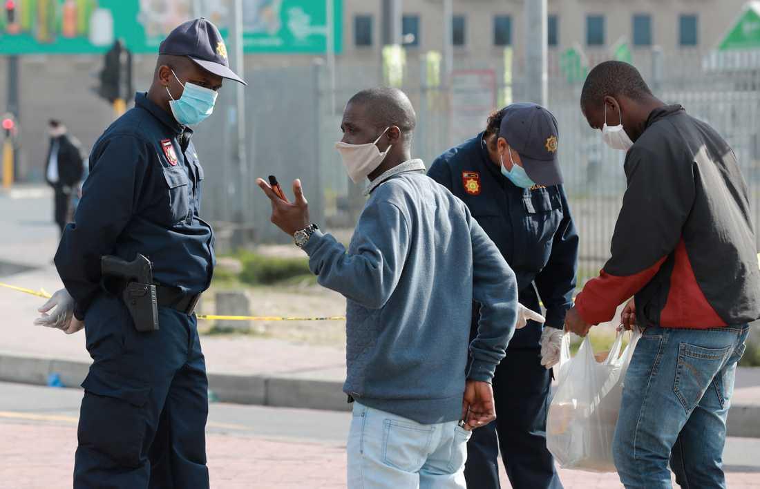 Sydafrikansk polis kontrollerar tillstånd vid en väntplats för taxibilar utanför Kapstaden.