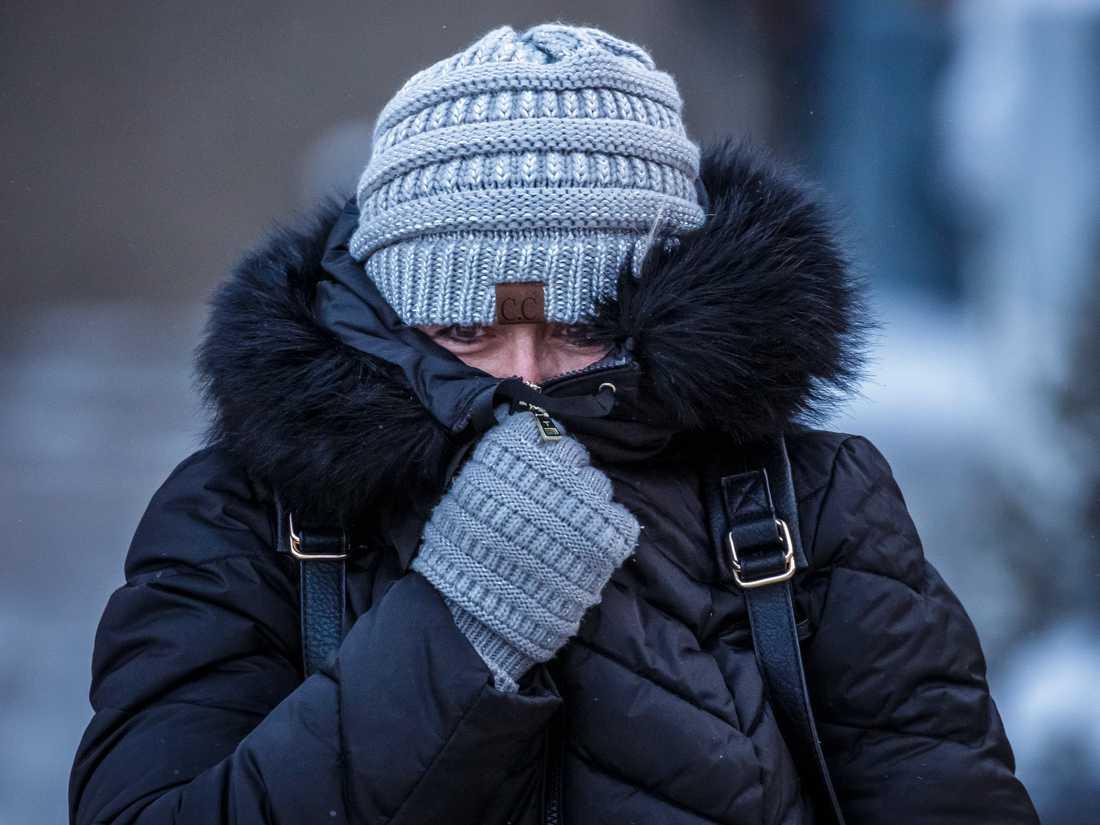 En kvinna i Rochester i Minnesota skyddar ansiktet mot kylan under en kort promenad på tisdagen. I flera stater i den amerikanska mellanvästern väntas de lägsta temperaturerna på flera generationer de kommande dagarna.