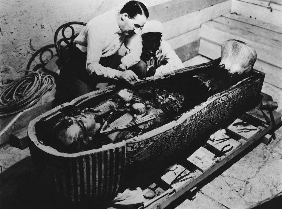 """Howard Carter vid Tutankhamuns sarkofag. Graven upptäcktes av Carter 1922, som när han kom in i graven yttrade de bevingade orden """"Jag ser underbara ting""""."""