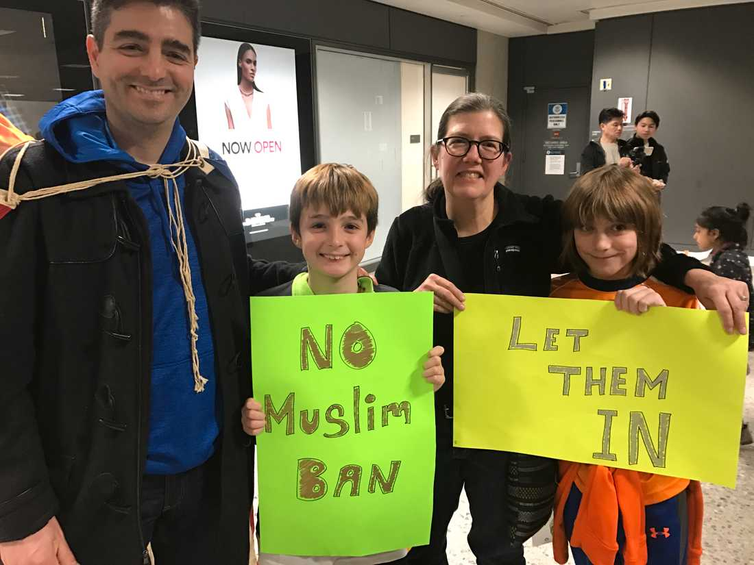 """Lucas Wall demonstrerar tillsammans med kompisen Darla Haney, sonen Matias och dennes vän Ben Hubble. """"Nej till muslimförbudet"""" och """"Låt dem komma in"""", står det på deras skyltar."""