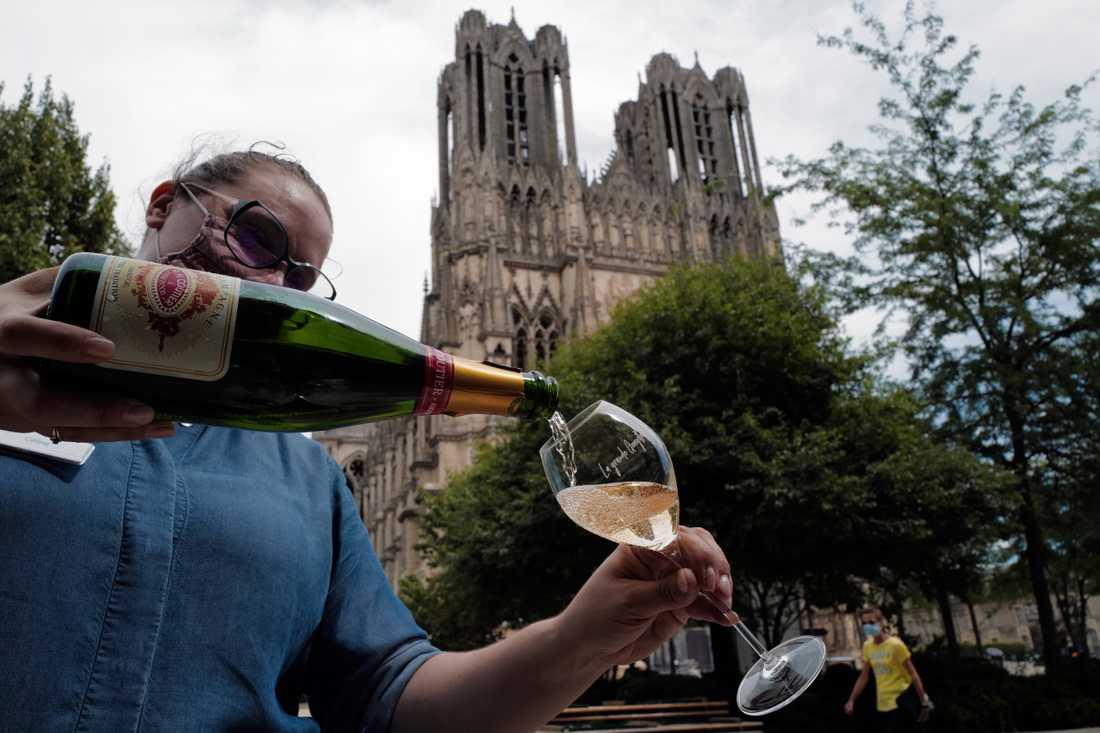 Ett glas champagne serveras i Reims i Frankrike – men marknaden ser mörk ut för vinproducenterna.