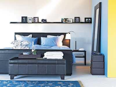 """Maskulint. Ett stilrent sovrum i svart, vitt och blått ger en lugn och harmonisk atmosfär. Sänggaveln """"Hampstead"""" i mörkbrunt läder med två sängbord, 10450 kr. Tavellisten """"Living"""" 190 kr. Sänglampan """"Saga"""", 990 kr. Sittbänken framför sängen kostar 2850 kr. Allt från Mio."""