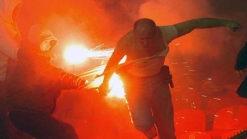 En civilklädd polis flyr för sitt liv på Röda Stjärnans hemmaarena i Belgrad.