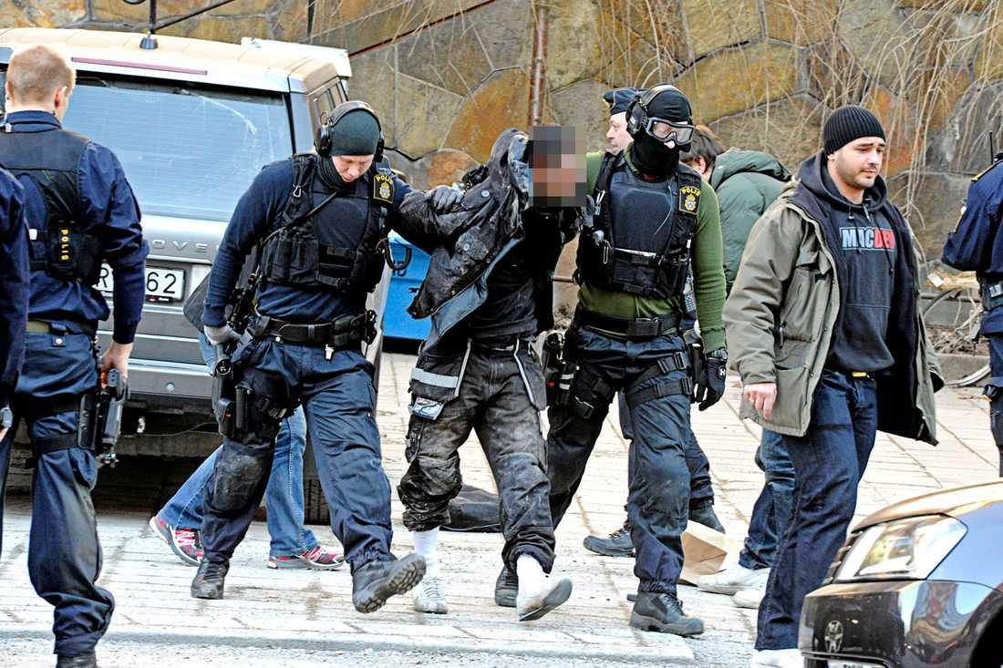 Polisen tar med sig en av rånarna.