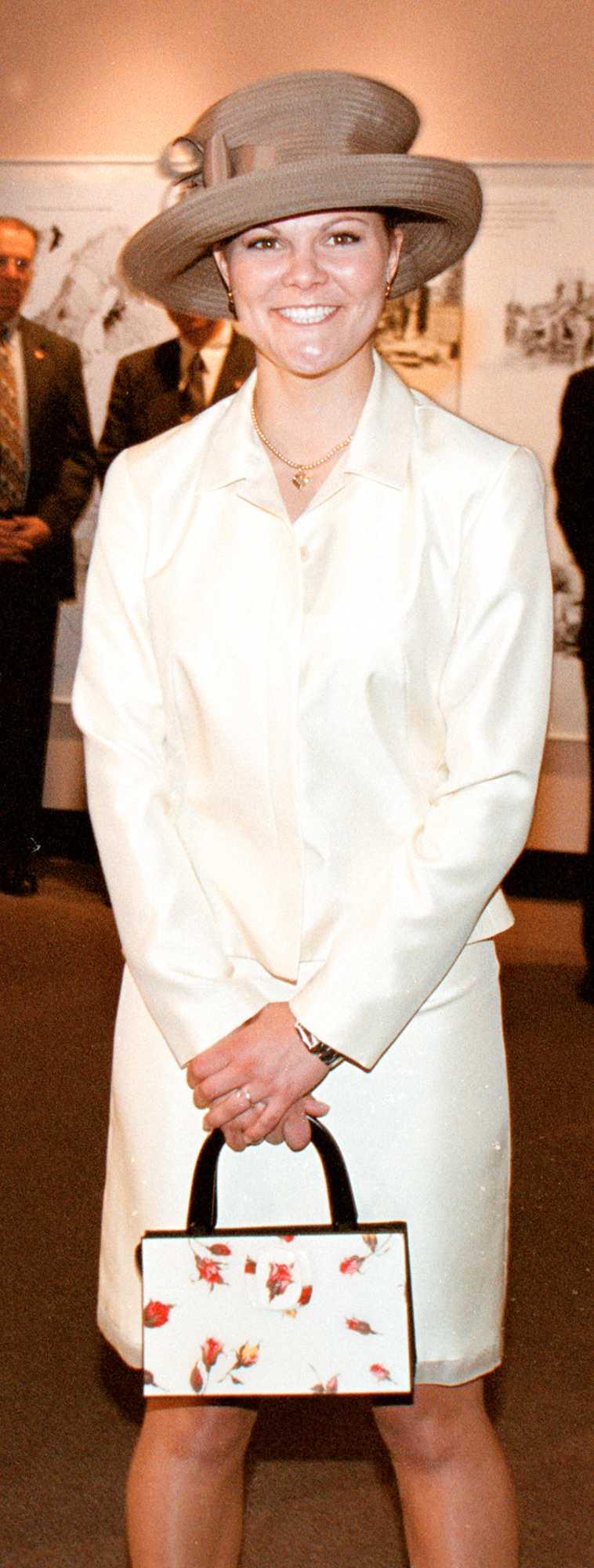 2000 I vit dräkt, stor hatt och den obligatoriska lilla handväskan inviger Victoria Vikingamuséet.