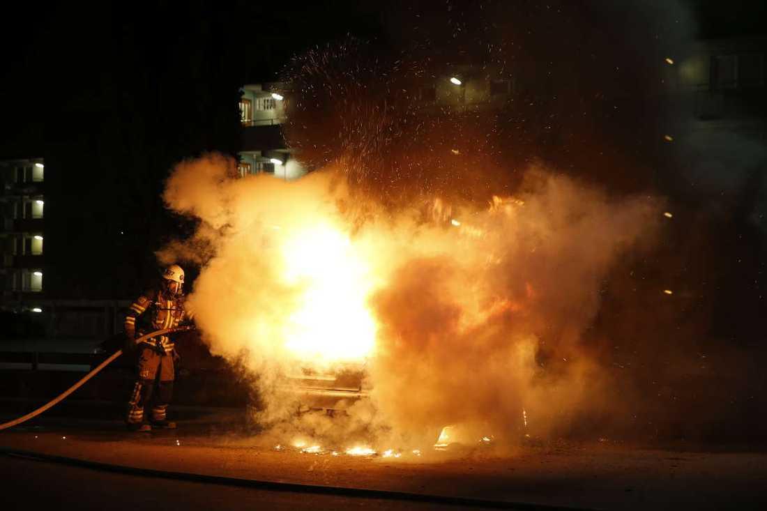 Brandman som släcker en brinnande bil i Husby