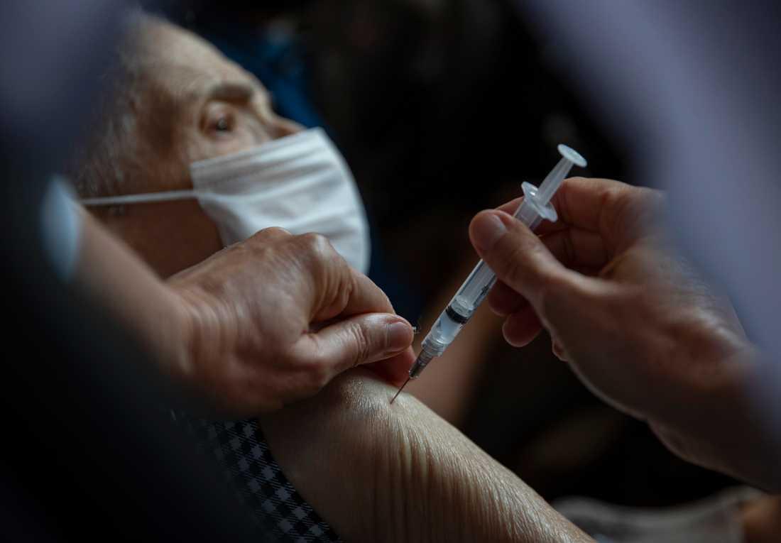 En vårdarbetare i Brasilien vaccinerar en äldre man med Sinovac.