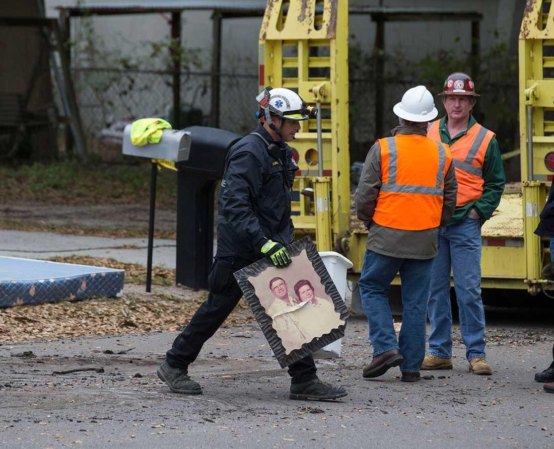 En byggarbetare lämnar huset med en tavla.