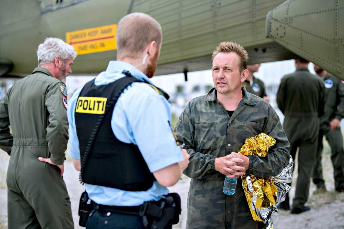 En till synes oberörd Peter Madsen har just räddats i land från sin förlista ubåt den 11 augusti. Han hävdar att han släppt av Kim Wall kvällen före. Till den samlade pressen gör han tummen upp som svar på frågan om han är okej.