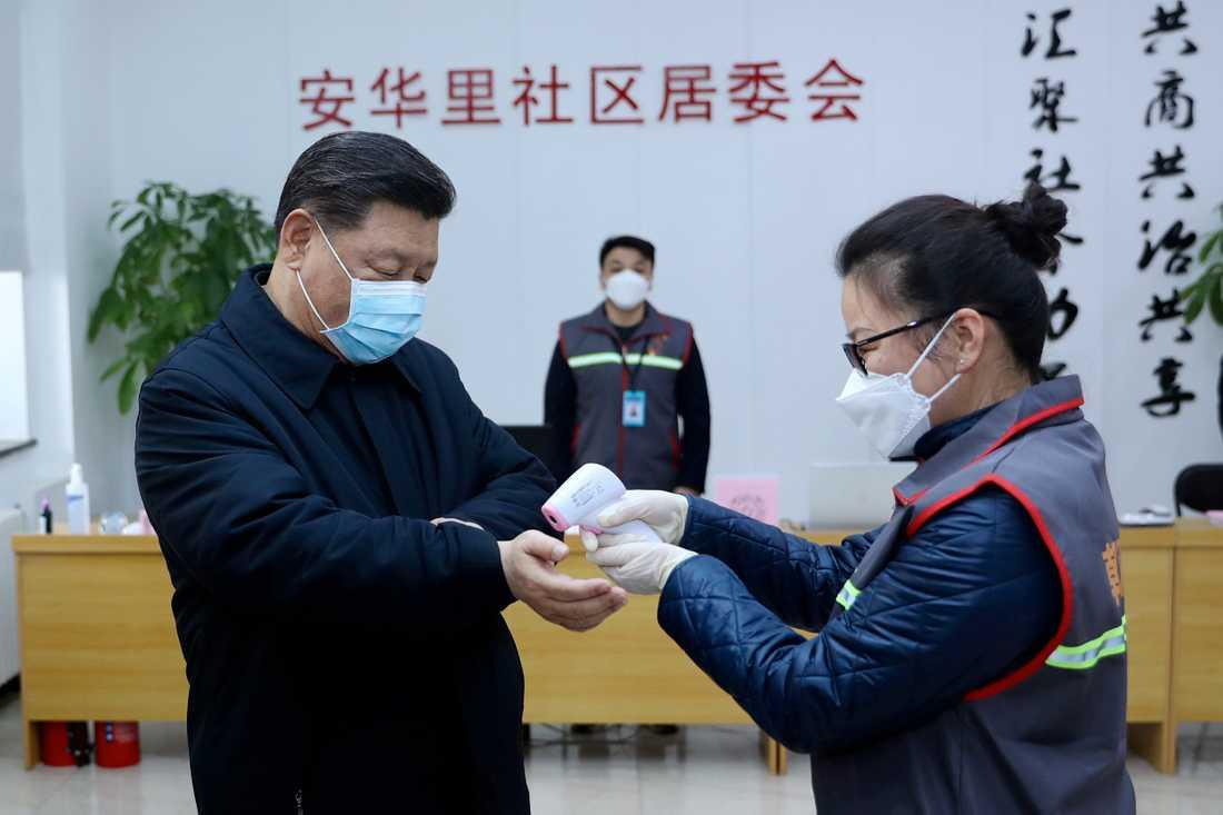 Kinas president Xi Jinping får temperaturen kontrollerad under ett besök på en vårdinrättning i Peking. Bild distribuerad av Kinas statliga nyhetsbyrå Nya Kina.