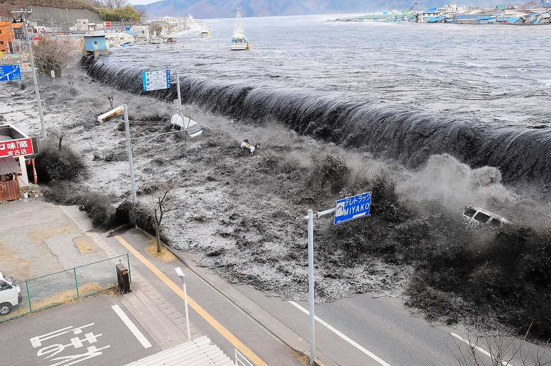 ORSAKEN Den enorma svarta tsunamivågen slår in över staden Miyako. Den drar med sig båtar från havet och krossar hus, bilar och bussar på land. Omkring 40 procent av Japans 35 000 kilometer långa kustlinje har skydd i form av säkerhetsvallar, men inget stoppade tsunamivågen i fredags.